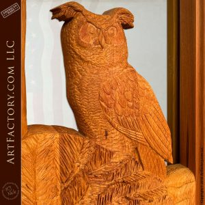 hand carved wood own on tree branch